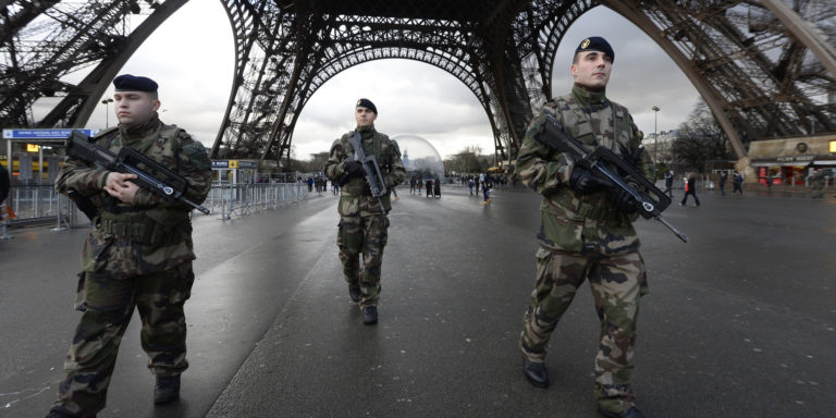 French soldiers patrol in front of the Eiffel Tower on January 8, 2015 in Paris as the capital was placed under the highest alert status a day after heavily armed gunmen shouting Islamist slogans stormed French satirical newspaper Charlie Hebdo and shot dead at least 12 people in the deadliest attack in France in four decades. A  huge manhunt for two brothers suspected of massacring 12 people in an Islamist attack at a satirical French weekly zeroed in on a northern town Thursday after the discovery of one of the getaway cars. As thousands of police tightened their net, the country marked a rare national day of mourning for Wednesday's bloodbath at Charlie Hebdo magazine in Paris, the worst terrorist attack in France for half a century. AFP PHOTO / BERTRAND GUAY